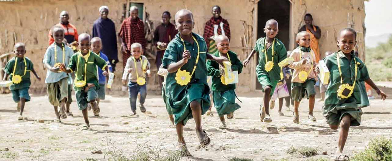 Outside a rural school building, children run energetically as adults watch in the background. The children wear Little Sun solar lamps on cords around their necks. The bright yellow lamps stand out against their green clothing.