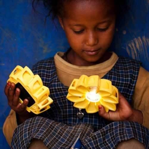 A school-girl in Ethiopia holds Little Sun solar lamps
