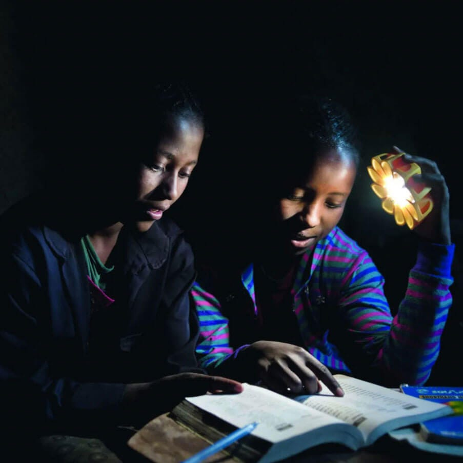School-children sit at a table in a darkened room. The light from a solar powered Little Sun lamp illuminates their books, meaning they can complete homework at night.